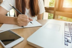 femme formation en ligne écrit au crayon de bois sur une feuille de papier devant ordinateur