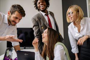 groupe de jeunes employés rigolent dans un bureau d'entreprise